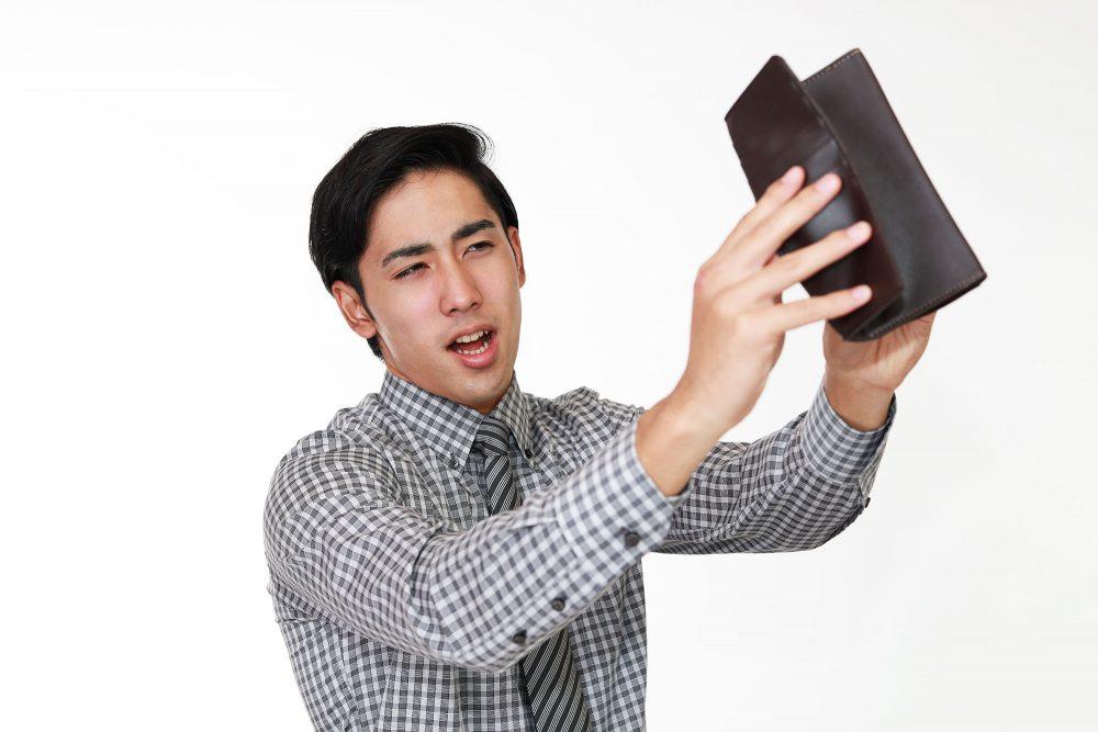 財布が空っぽで嘆く男性